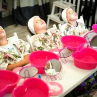 Little girls sit in a row and get facials as part of a spa party for little girls