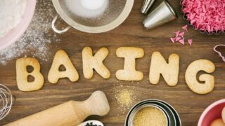 The word BAKING is spelled out in letter shaped cookies on a counter with baking ingredients and accessories nearby