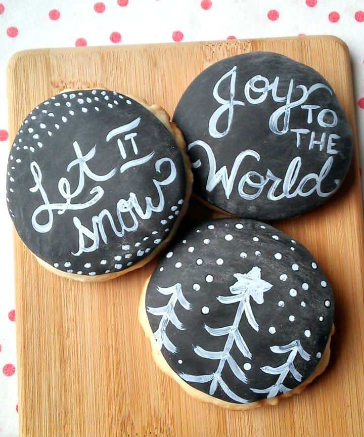 Three sugar cookies are displayed on a wooden cutting board.  The cookies are covered in black fondant and decorated to look like chalkboards, with holiday messages and decorations for Christmas.