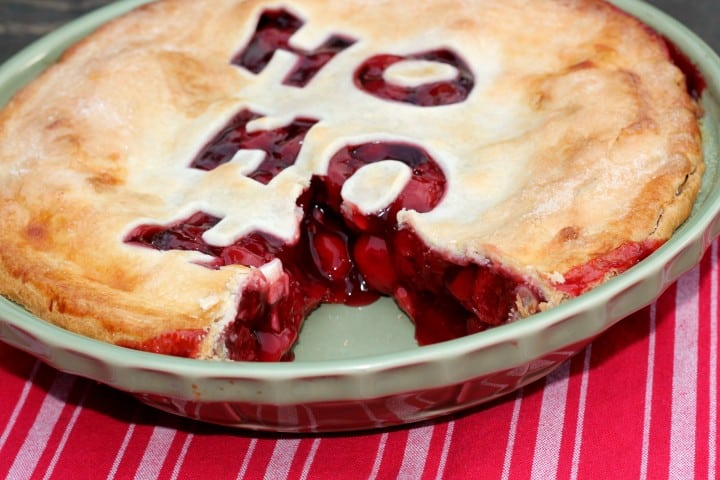 Christmas Cherry Pie for the holidays. A cherry pie with a slice cut out of it. You can see the detailed decoration on top, which is a Ho Ho Ho cut out.