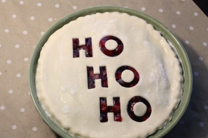 A Christmas cherry pie with the words Ho Ho Ho cut out of the top before being baked. The pie is sprinkled with sugar.