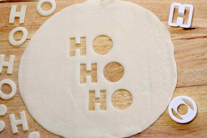 A process photo of making Christmas cherry pie crust with  a Ho Ho Ho cut out. The pie crust is on a wooden cutting board after having the letters cut out.