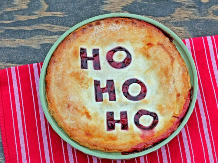 A Christmas cherry pie for the holidays. A Cherry pie with the letters Ho Ho Ho cut out  from the top crust sits on a wooden table and festive red table cloth.