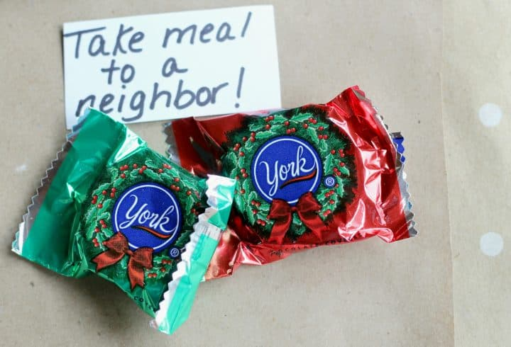 "Two York peppermint patty candies and a handwritten instruction  to ""Take a meal to a neighbor"" as part of a random act of kindness advent calendar"