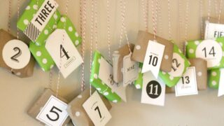 A DIY advent calendar made from kraft paper and scrapbook paper hanging on a wall from a pole