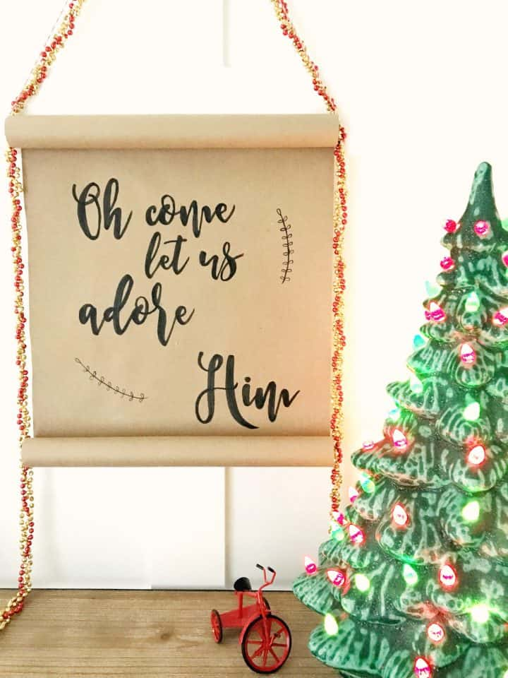 "A hand lettered Christmas scroll made from kraft paper hangs against a white wall next to  a vintage  Christmas ceramic tree. The text on the scroll says, ""Oh Come Let Us Adore Him"""