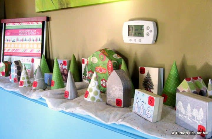 A homemade random acts of Christmas kindness advent calendar made to look like a cardboard village