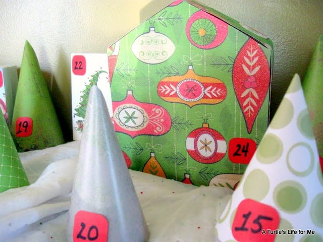 A homemade advent calendar made to look like a village  of houses and trees.