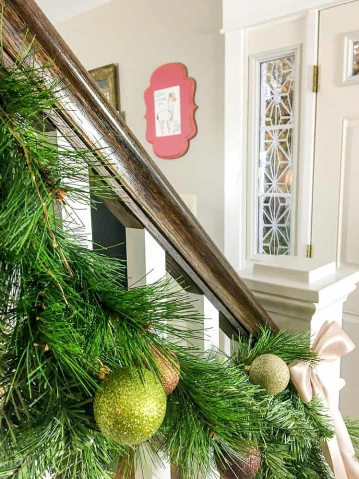 how to make faux evergreen staircase garland with copper LED Christmas lights