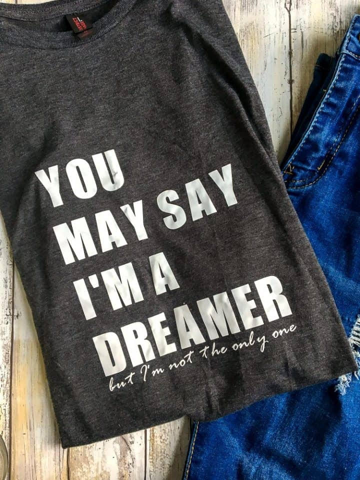 How to make a band t shirt with Cricut vinyl. A dark grey tshirt with the lyrics You May Say I'm a Dreamer but I'm Not the Only One folded on a plank table with jeans in frame