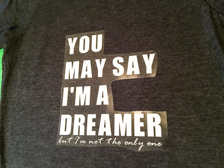 How to make a band tshirt with vinyl. A process shot showing the lyrics You May Say I'm a Dreamer but I'm Not the Only One made into a Cricut vinyl transfer with white text before being ironed onto a grey tshirt