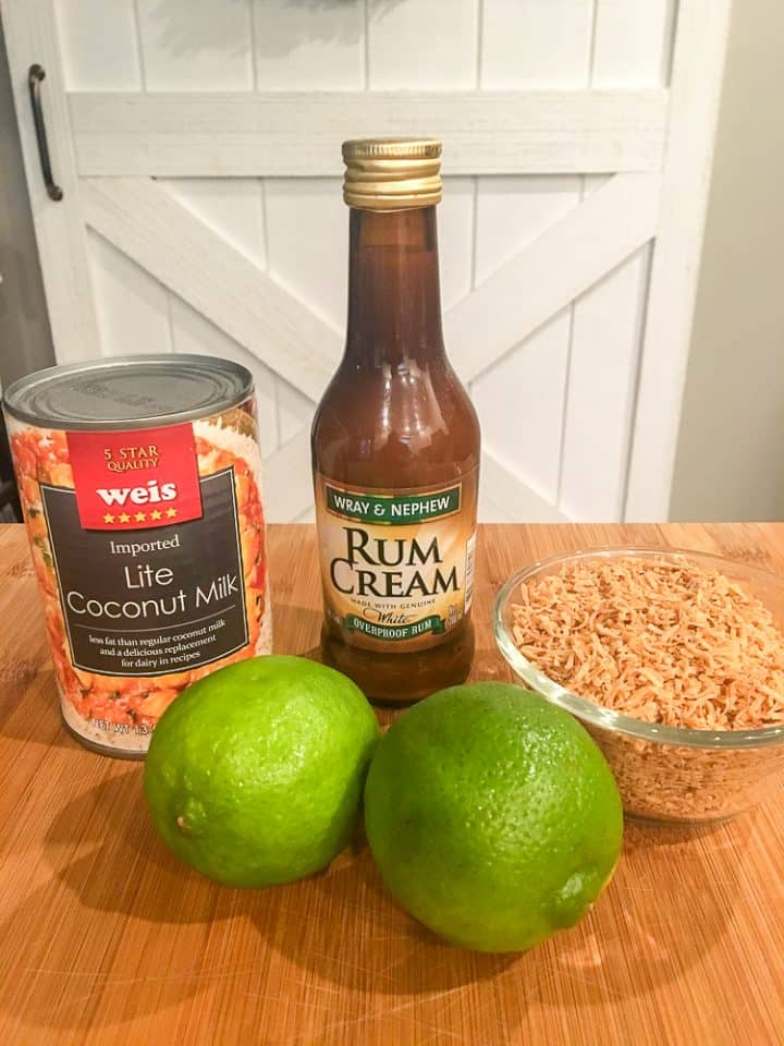 Coconut Lime Cocktail with Rum Recipe Ingredients sit on a wooden countertop. Ingredients include a can of lite coconut milk, 2 limes, a bottle of Run Cream, and toasted coconut flakes