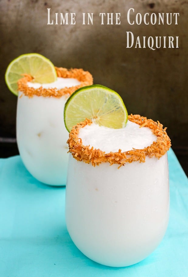Coconut Lime Daiquiri Cocktail with Rum Recipe Pinterest Pin. The image shows two stemless wine glasses with the drink, and the glasses are rimmed with toasted coconut flakes and lime wedge. The text says Lime in the Coconut Daiquiri