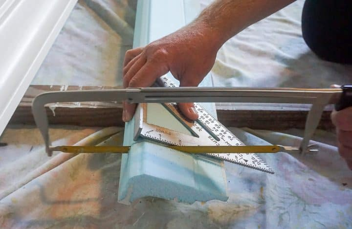 cutting a piece of foam crown molding with a hacksaw