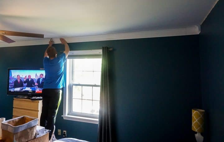 guy standing on a ladder holding a piece of crown molding in place