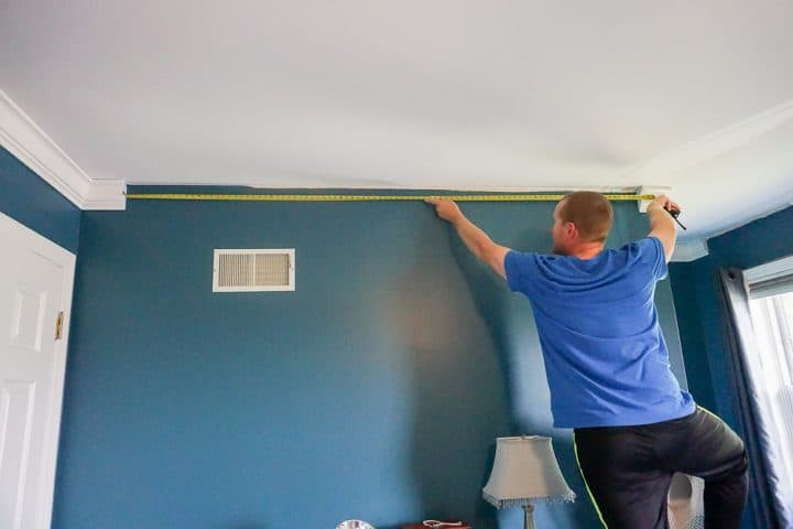 guy measuring a space between two pieces of crown molding