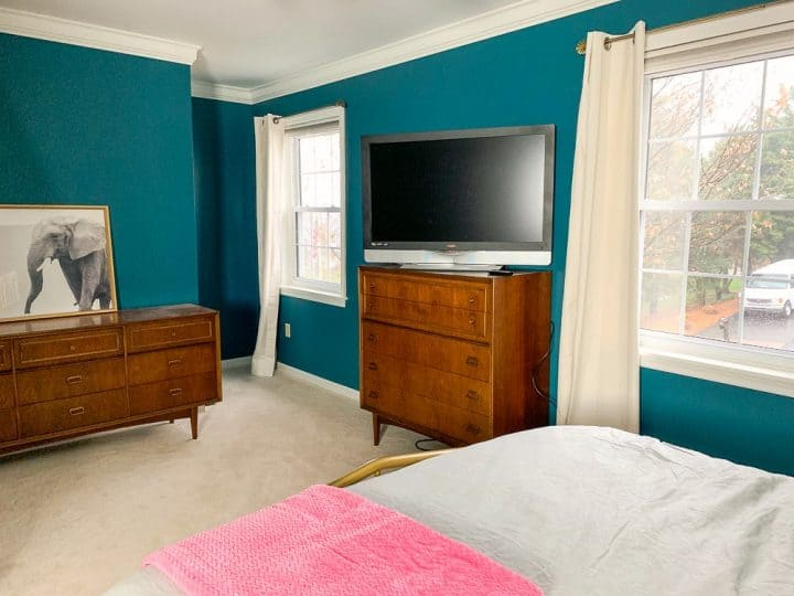master bedroom with teal walls and mid century modern dressers