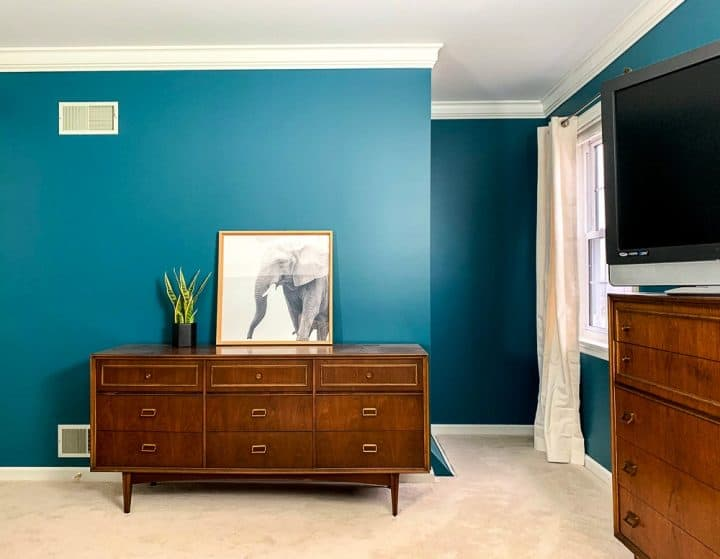 bedroom with teal walls and mid century modern furniture
