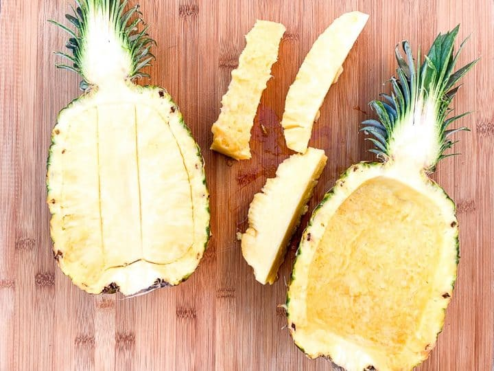 a process shot showing how to grill a pineapple boat. A halved and scored pineapple on a wooden cutting board