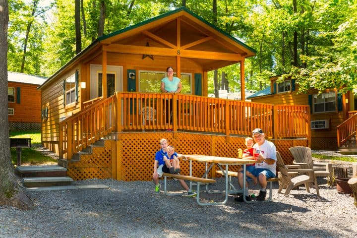 full-service cabin at Yogi Bear jellystone campground with picnic bench out front