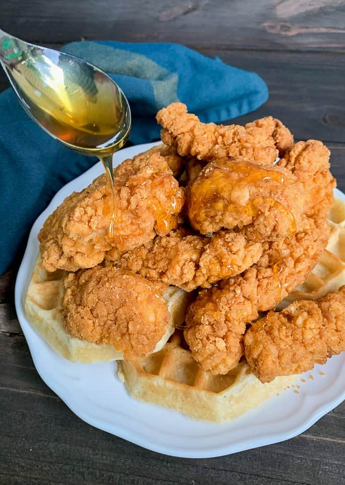 crispy chicken and waffles with a spoon drizzling honey