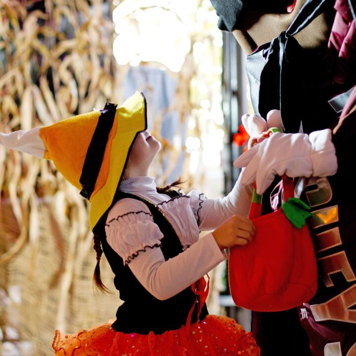 a girl dressed as a witch getting candy from a costume character