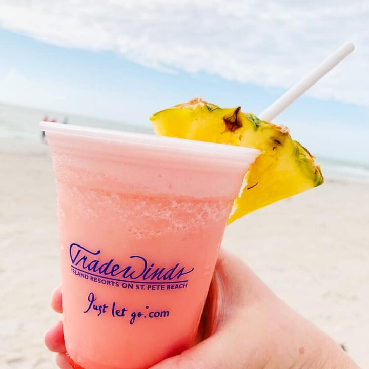 pink frozen drink with a pineapple garnish on the beach
