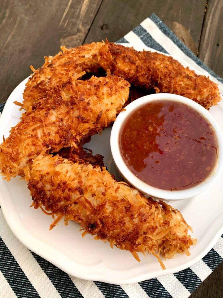 white plate with 4 coconut chicken tenders and small bowl of chili dipping sauce