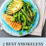 """A Pinterest pin with an image of grilled chicken breast, grilled avocado, and green salad on a blue plate. The plate is sitting on a cloth napkin on a grey table. The text says, """"7 Best Smokeless Indoor Grills."""""""
