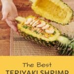 A pinterest pin with an image of a pineapple boat filled with a shrimp and rice bowl. The text says The Best Teriyaki Shrimp Pineapple Boats.