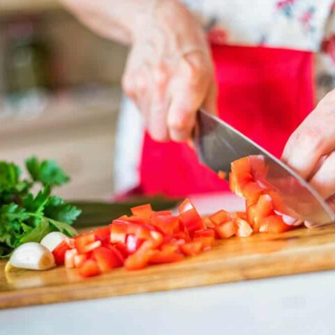 A female hand with a kitchen knife dicing tomatoes at home