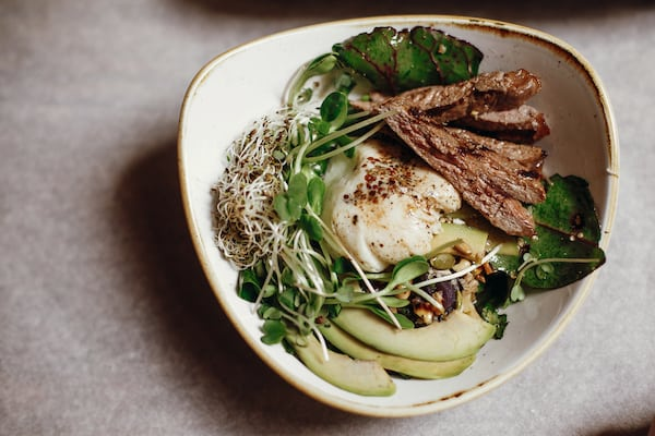 Delicious salad with juicy grill steak, avocado, sprouted greens, leaves, egg pouch, nuts in stylish bowl on a table.