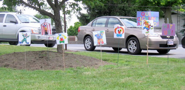 An outdoor backyard party game for kids is set up on the lawn of a school, with  cars parked in the background. The game shows clown images on garden stakes  driven into the grass.