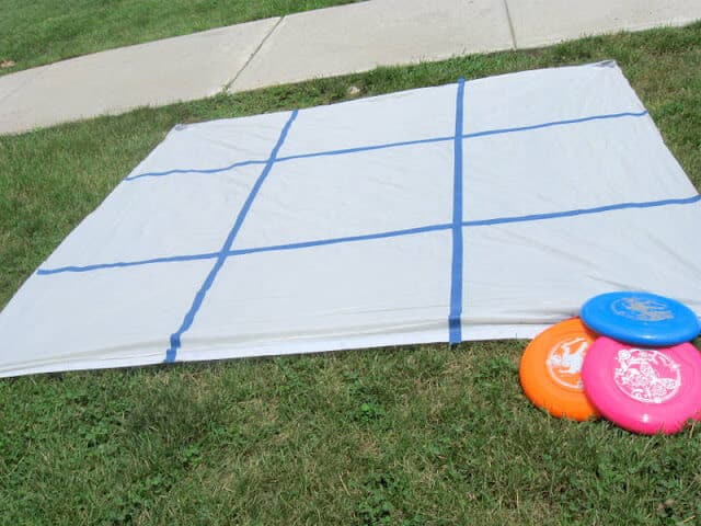 A game board to play backyard frisbee tic tac toe is made out of a shower curtain and painters tape and is set on a green lawn