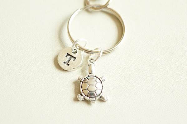 A small silver turtle keyring with an initial F