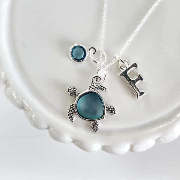 A silver and blue  stone pendant necklace in the  shape of a turtle, with a small stone and letter F hanging off the chain  as well.