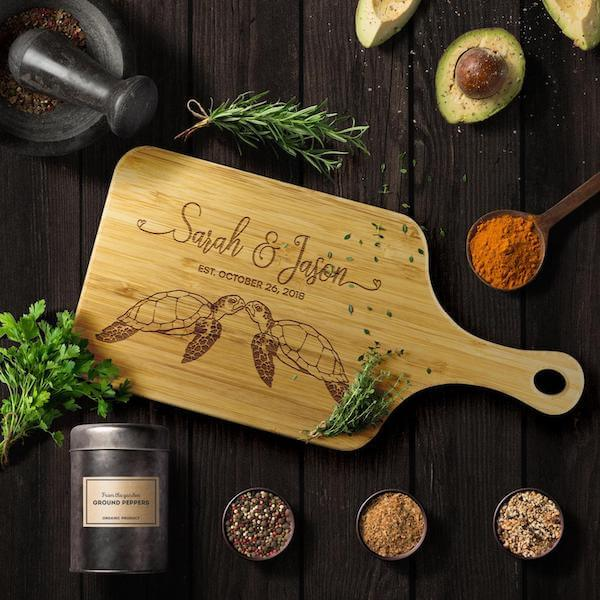 A personalized bamboo cutting board with  engraved  names, a date, and two kissing sea turtles. The cutting board sits on a dark wood table with spices and food around it.