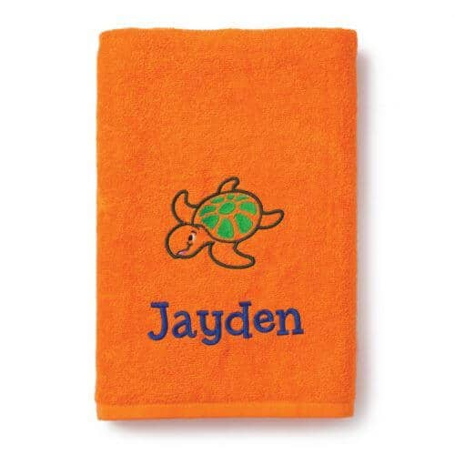 An orange bath towel with an embroidered cartoon  turtle and a name.