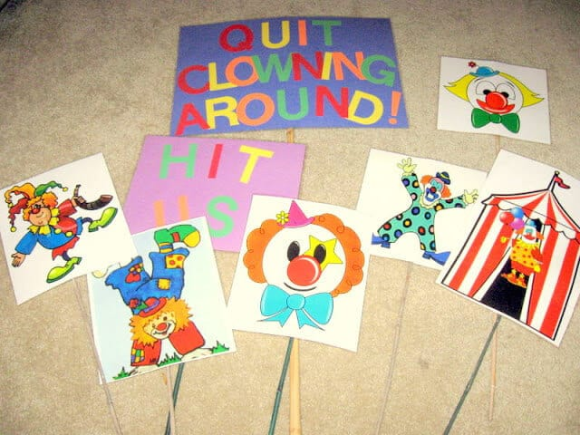 Clown images are colored, laminated, and attached to garden stakes as part of an outdoor end of year school party game.