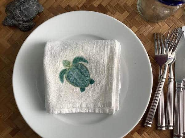 A hand painted sea turtle on a white cloth napkin. The napkin is folded on a white plate, and the plate  is on a wooden table with cutlery to the side.
