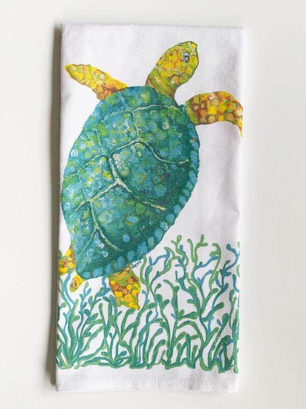 Original sea turtle art in hand painted style with green and yellow on a white kitchen tea towel.