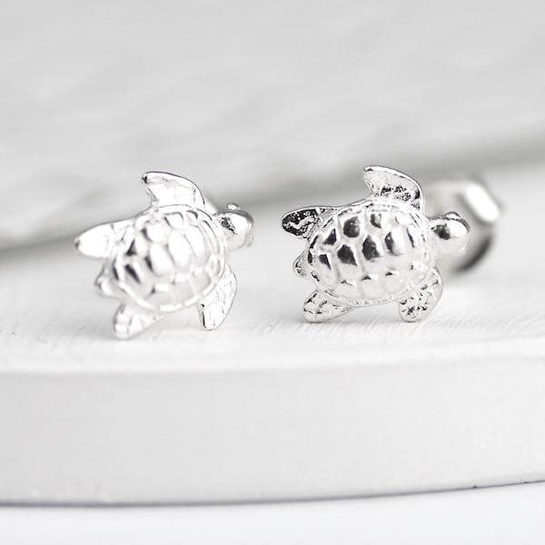 Sterling silver turtle stud earrings on  a white marble background