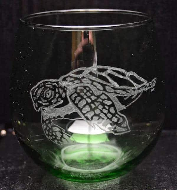 A hand etched sea turtle on a clear stemless wine glass