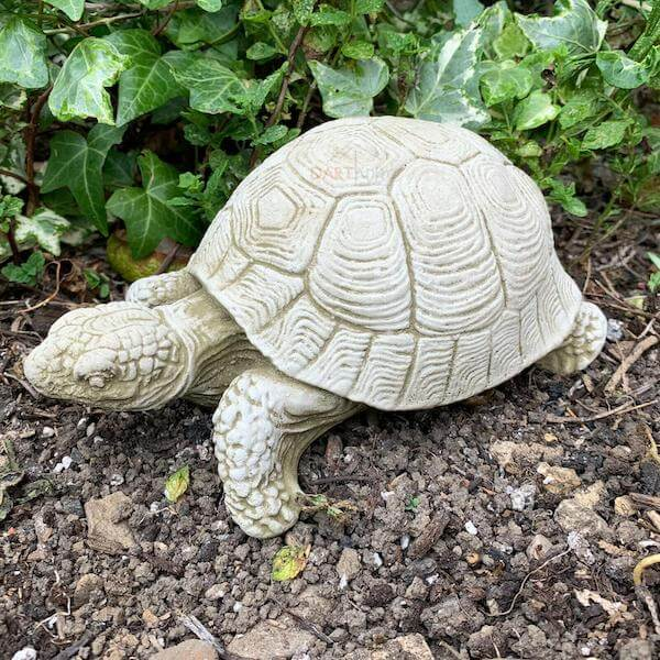 A stone sculpture of a tortoise in a garden