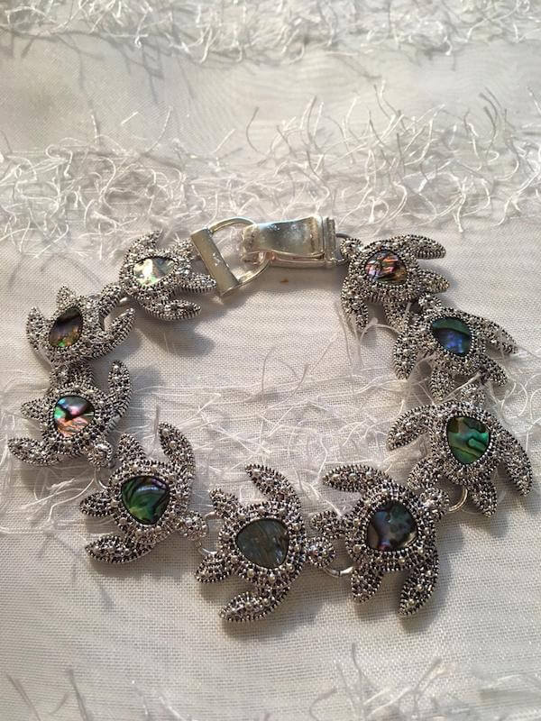 A silver turtle bracelet made of silver turtle and crystal shapes  linked together
