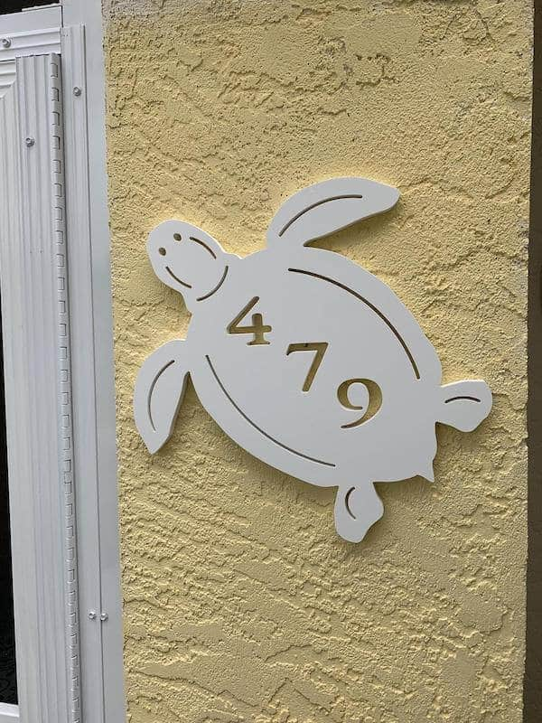 An  address plaque in the shape of a turtle on a  house front.