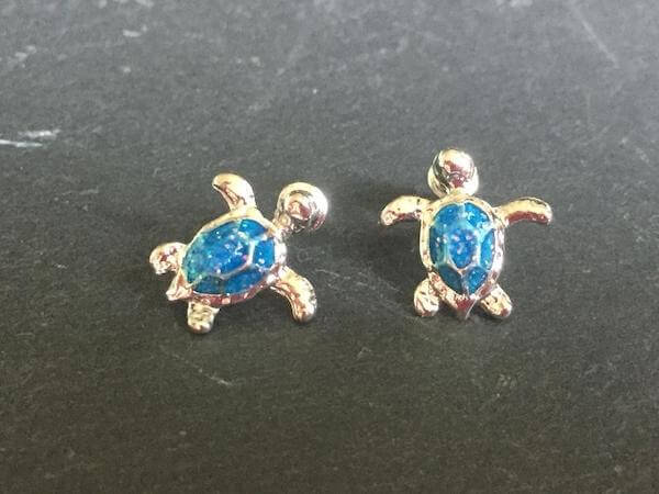 Silver stud turtle earrings with blue opal shells on a grey  countertop