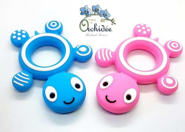 Pink  and blue teething rings shaped  like  turtles against an isolated white background