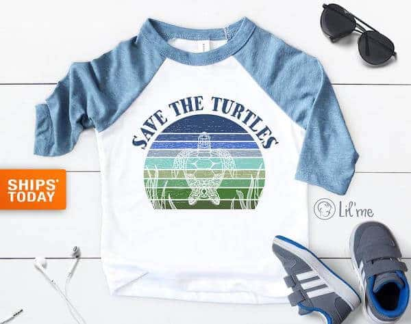 A baseball style toddler tshirt in white and blue with a Save the Turtles graphic design
