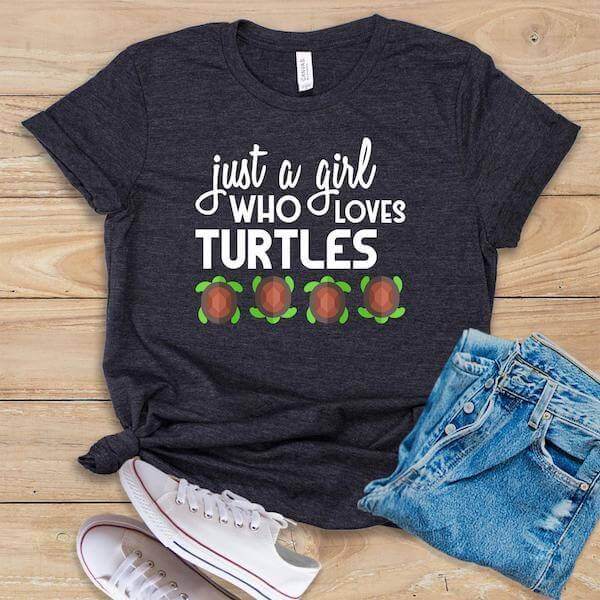 A grey tshirt that says Just a Girl Who Loves Turtles against  a  wooden background. There is a pair of folded jeans and white shoes.